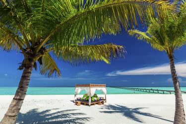 Tropical white beach, beautiful blue sky, palm trees and place to relax